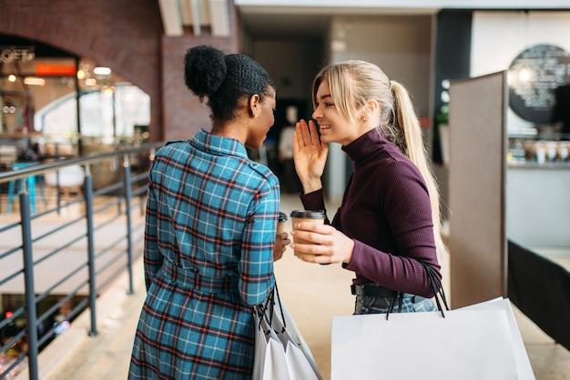 モールで買い物袋を持つ白と黒の女性。
