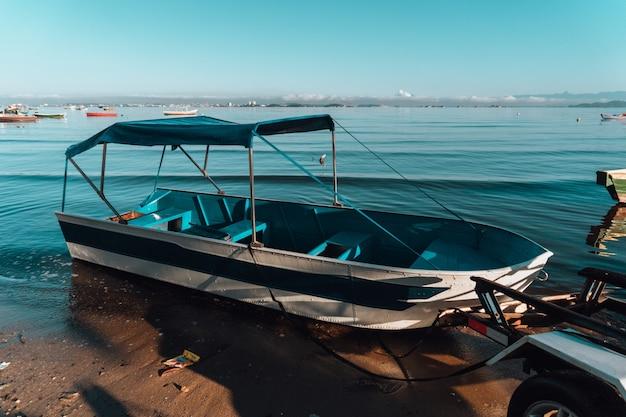 Бело-синяя лодка на берегу в рио