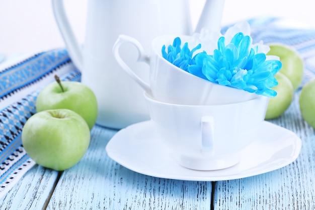 テーブルのクローズアップに食器と白と青の菊