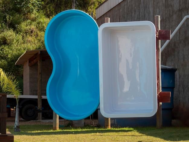 Белые и синие бассейны из стекловолокна выставлены на продажу.