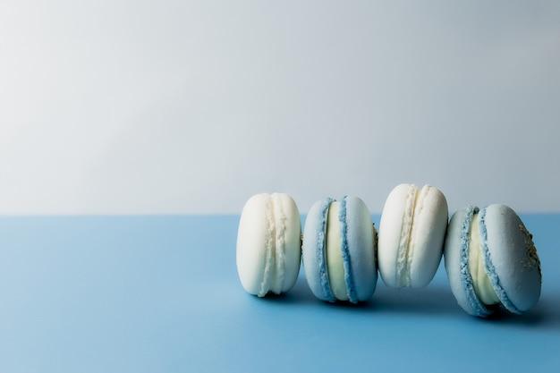 테이블에 흰색과 파란색 마카롱, 파란색 배경에 마카롱. 고품질 사진
