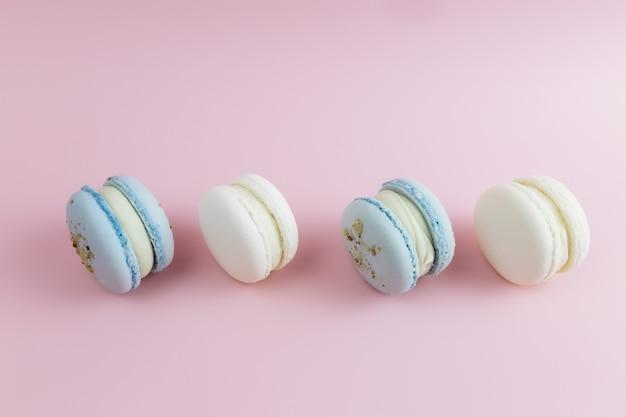 테이블에 흰색과 파란색 마카롱, 분홍색 배경에 마카롱.