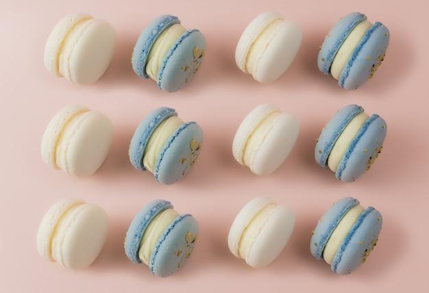 테이블에 흰색과 파란색 마카롱, 분홍색 표면에 마카롱. 고품질 사진