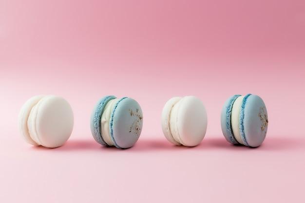 Белые и голубые миндальное печенье на столе, миндальное печенье на розовом столе.
