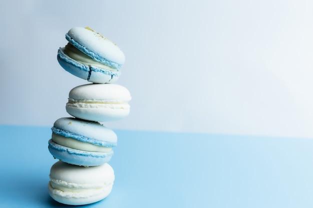 테이블에 흰색과 파란색 마카롱, 흰색 파란색 배경에 마카롱.