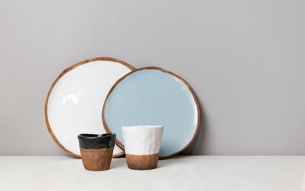 흰색과 파란색 둥근 접시, 흰색과 검은색 테두리가 있는 두 개의 갈색 머그, 린넨 식탁보와 회색 벽 배경이 있는 테이블. 주방 미니멀한 현대적인 소박한 식기 컨셉입니다. 수제 세라믹