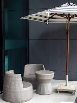 현대 회색 등나무 의자와 건물 근처 테이블 근처 야외 생활에 흰색과 파란색 줄무늬 패브릭 비치 파라솔.