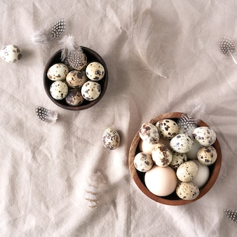 흰색과 갈색 부활절 달걀, 메 추 라 기 계란과 자연 린 넨 배경에 깃털. 부활절 배경.