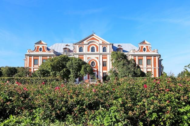 Белое и коричневое старое здание за цветущими кустами роз на фоне голубого неба