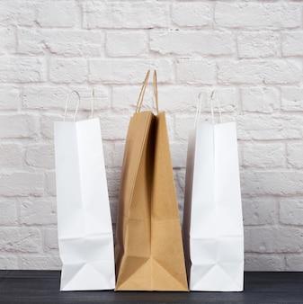 Белые и коричневые бумажные пакеты с ручками на фоне белой кирпичной стены