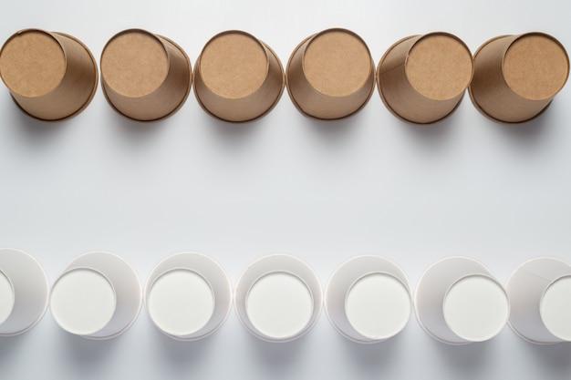 밝은 배경에 흰색과 갈색 종이컵이 거꾸로 뒤집 혔습니다.