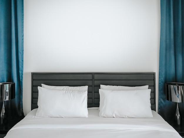 블루 커튼 사이의 빈 공간 흰색 벽이있는 호텔 침실에서 침대에 부부를위한 흰색과 깨끗한 베개.
