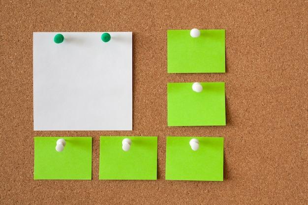 코르크 판에 메모를 위해 흰색과 녹색 용지 5 장. 비즈니스 개념. 공간을 복사하십시오.