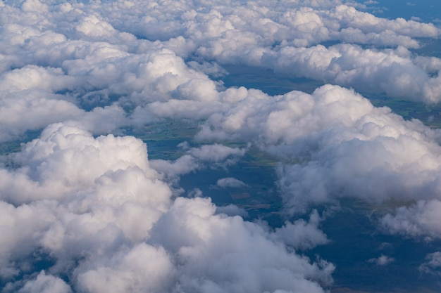 아래에 보이는 땅과 함께 하늘에서 흰색과 솜털 구름보기