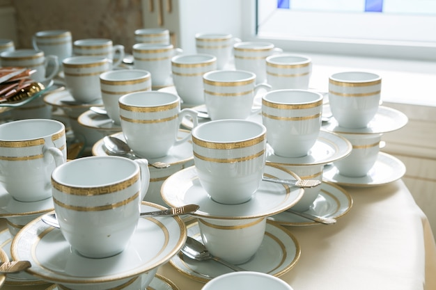 흰색과 금색 머그잔, 접시가 있는 차 또는 커피용 컵, 서로 서 있는 것