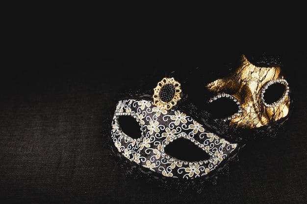 Белые и золотая маска на темном фоне