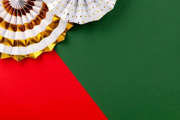 빨간색 배경에 흰색과 황금 종이 팬.