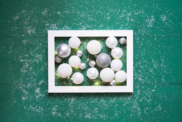 Белые и серые воздушные шары с горящей гирляндой лежат в белом в рамке на зеленом деревянном фоне