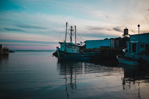 昼間の水の体に白と灰色の漁船