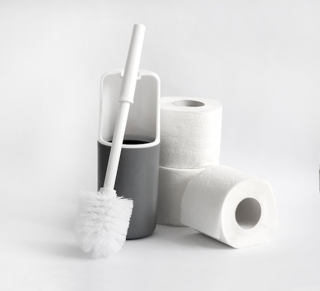 白と灰色のプラスチック製トイレブラシと白い背景の上のトイレットペーパーのロール