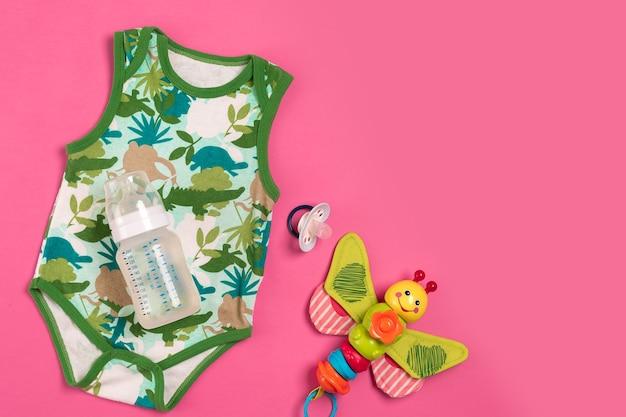 Бело-зеленый комбинезон и бутылка на розовом фоне. вещи для младенцев. вид сверху. скопируйте пространство. плоская планировка. натюрморт