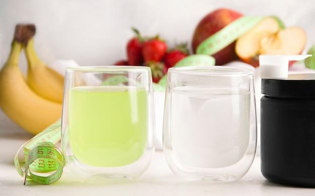 안경을 쓴 운동선수를 위한 흰색과 녹색 음료. 흰색 배경