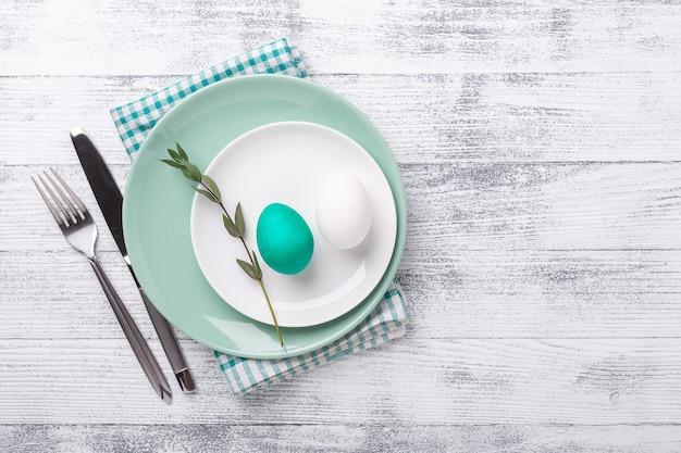 Белая и зеленая мятная тарелка с пасхальными яйцами и столовыми приборами на деревянных фоне. пасхальная композиция. скопируйте пространство. вид сверху - изображение