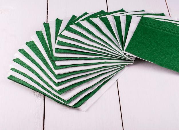 Бело-зеленые салфетки для обеденного стола на светлом деревянном столе