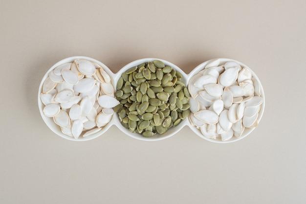 Белые и зеленые тыквенные семечки в белых чашках.