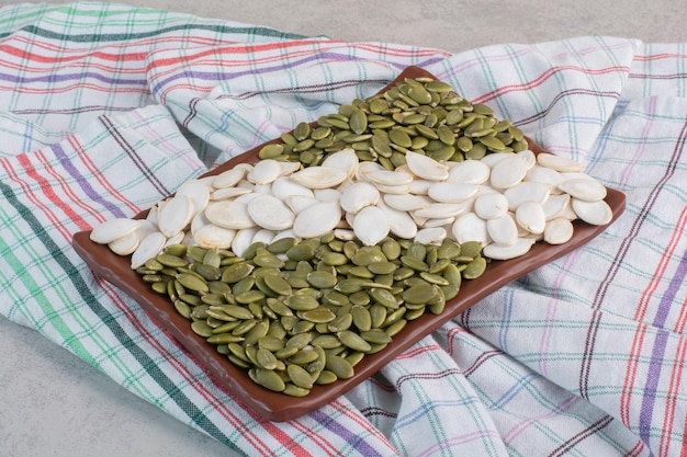 콘크리트 표면에 흰색과 녹색 호박 씨앗.