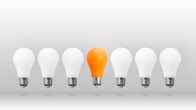 白い背景の上を飛んでいる白とオレンジの省エネ電球。箱から出して考えるという概念から、違います。