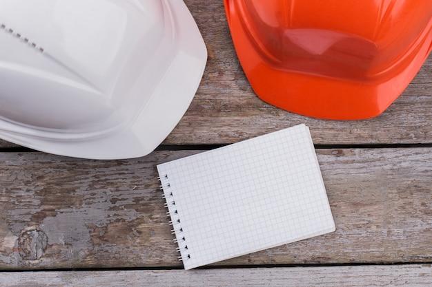 Белые и оранжевые пластиковые шлемы строителей. пустой блокнот для копирования пространства. старый деревянный фон.