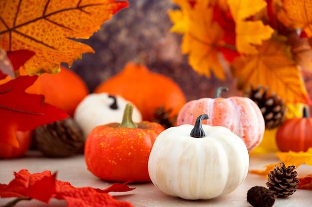 秋の黄色の葉と松ぼっくりの白とオレンジのカボチャの組成。秋のコンセプト。