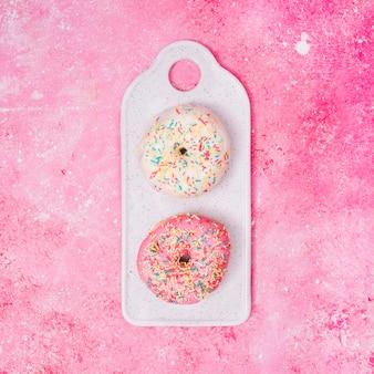 ピンクのテクスチャ背景の上のトレイにカラフルな振りかけると白とピンクのドーナツ