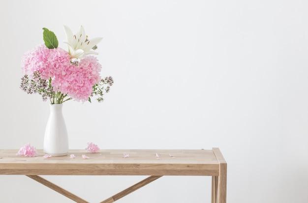 나무 선반에 흰색 꽃병에 흰색과 분홍색 꽃