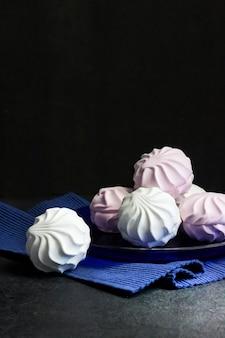 검정색 배경에 파란색 접시에 흰색과 분홍색 마시멜로