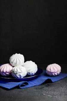 검정색 배경에 파란색 접시에 흰색과 분홍색 마시멜로.