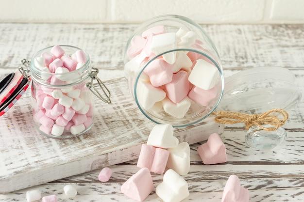 ボウルに入れてローストするための白とピンクのマシュマロとホットチョコレートをクローズアップします。冬の食べ物の背景の概念。