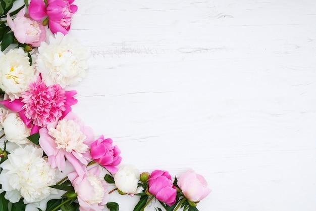 Белые и розовые пионы граничат на белом деревянном фоне. копирование пространства, вид сверху. день матери, день святого валентина, концепция дня рождения. открытка.