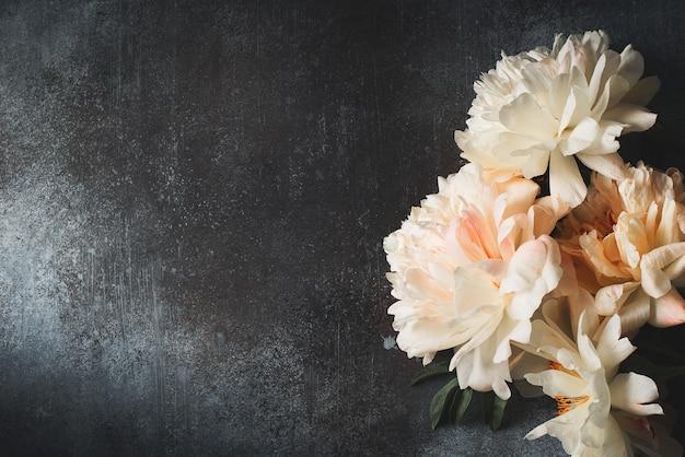 Рамка из белых и розовых пионов на темном фоне, открытка, копия пространства, вид сверху