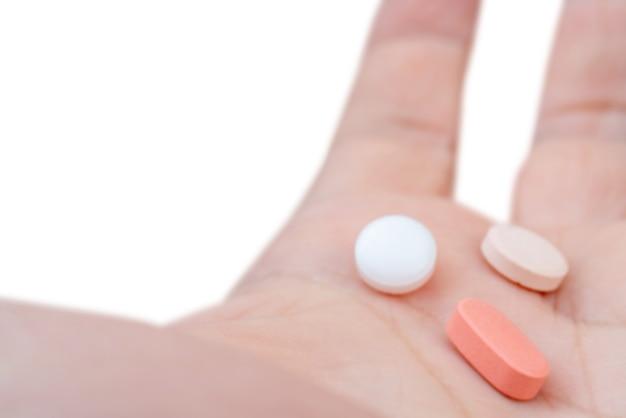 Белые и розовые таблетки на ладони. лечение таблетками.