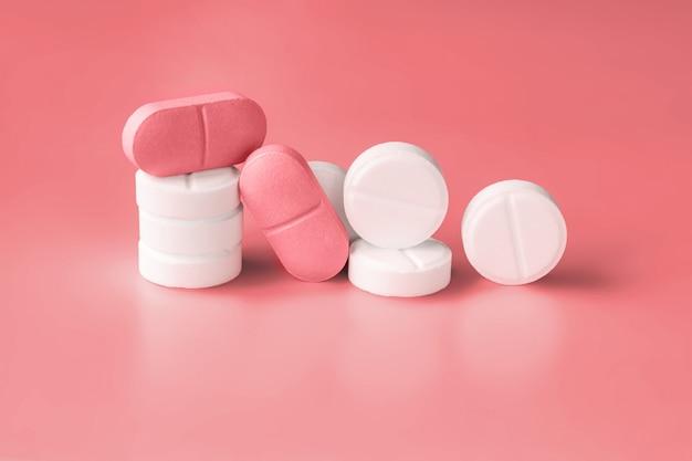 Белые и розовые таблетки на красном фоне продукты для похудения, витамины, гормоны или седативные средства