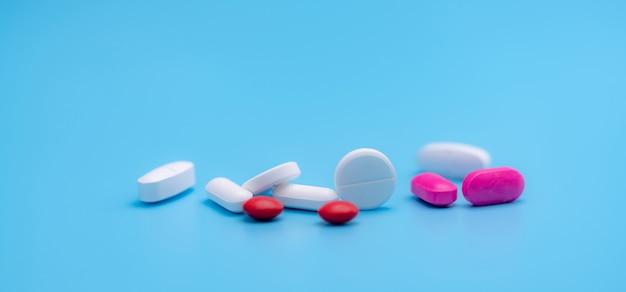 青で分離された白とピンクの錠剤の丸薬