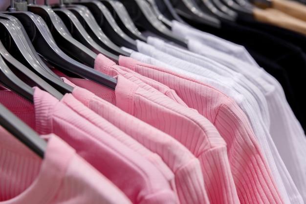 モールのハンガーに掛かっている白とピンクの t シャツの服