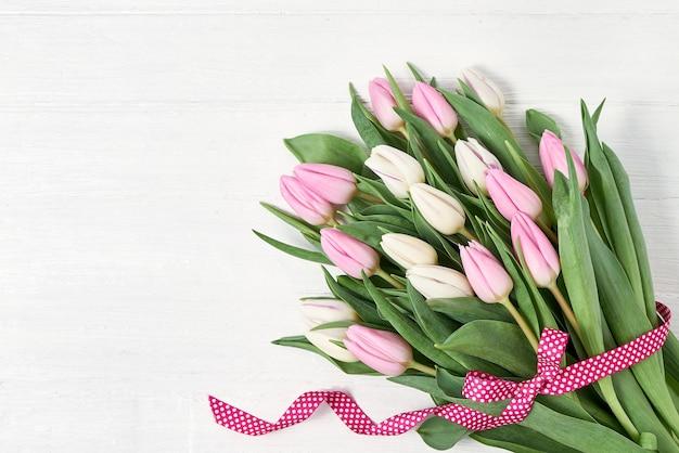 Букет белых и розовых тюльпанов украшен лентой. копировать пространство