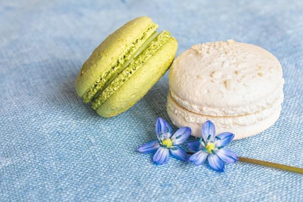 Белое и фисташковое миндальное печенье и весенний цветок на льняной салфетке.