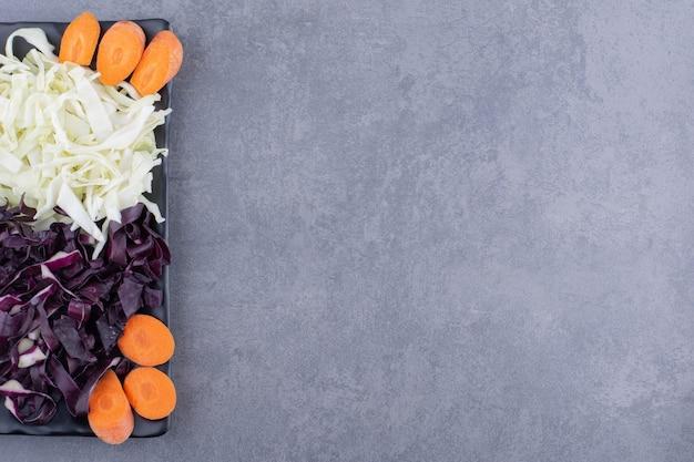 당근을 곁들인 흰색과 보라색 다진 양배추