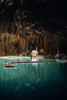 낮 동안 호수에 흰색과 빨간색 보트