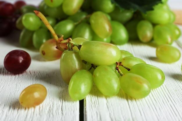 Белый и красный виноград на белой поверхности деревянной поверхности