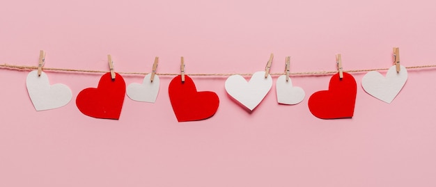 孤立したピンクの背景、愛とバレンタインのコンセプトのロープに白と赤のハートピン